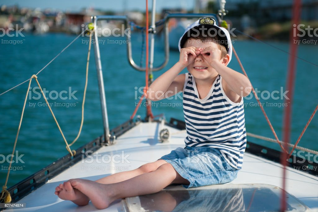 happy kid captain sitting on luxury boat with sea background behind stock photo