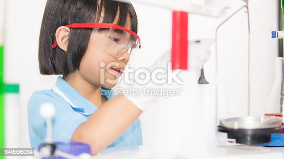 istock Happy kid child girl on playing and learning science laboratory 949596034