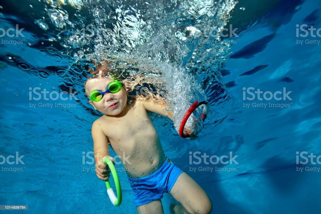 245692b79 Niño feliz hacer deporte y nadar bajo el agua en la piscina sobre un fondo  azul
