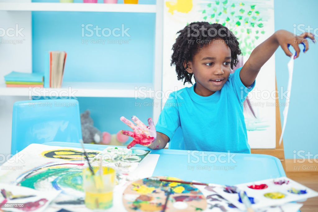 Happy kid enjoying arts and crafts painting foto stock royalty-free