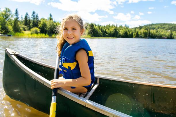 Happy kid enjoying canoe ride on beautiful river A Happy kid enjoying canoe ride on beautiful river canoeing stock pictures, royalty-free photos & images