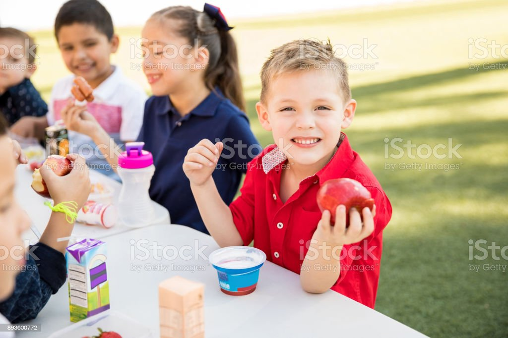 Happy kid enjoying lunch time at school stock photo