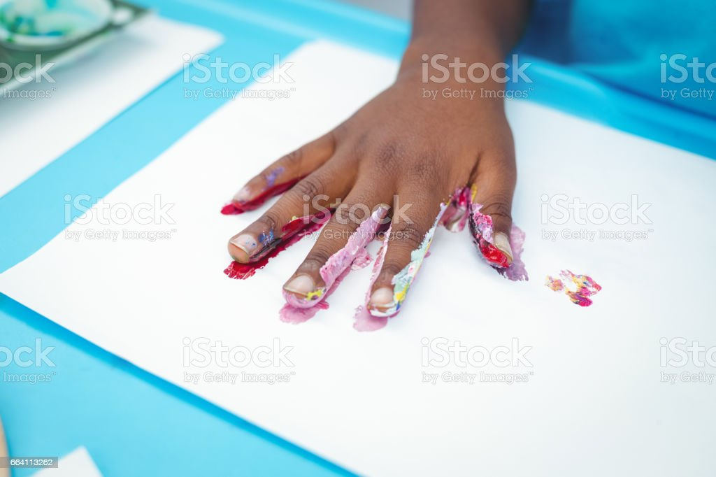 Happy kid enjoying painting with his hands foto stock royalty-free
