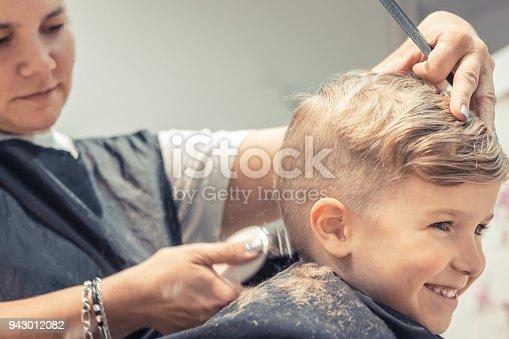 Smiling little boy enjoying while having a haircut at the salon.