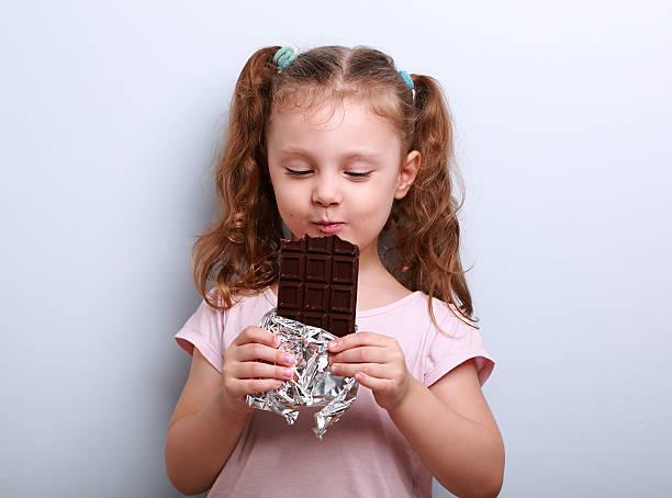 glückliches kind mädchen essen fitness dunkler schokolade mit vergnügen - kinderschokolade stock-fotos und bilder