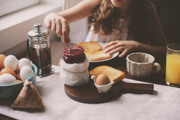 happy kid girl having breakfast at home, eating toast with jam and eggs on farmhouse kitchen stock photo
