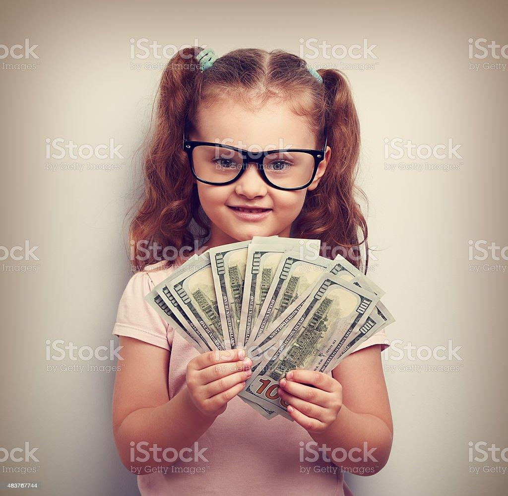 Happy kid girl in glasses holding money stock photo