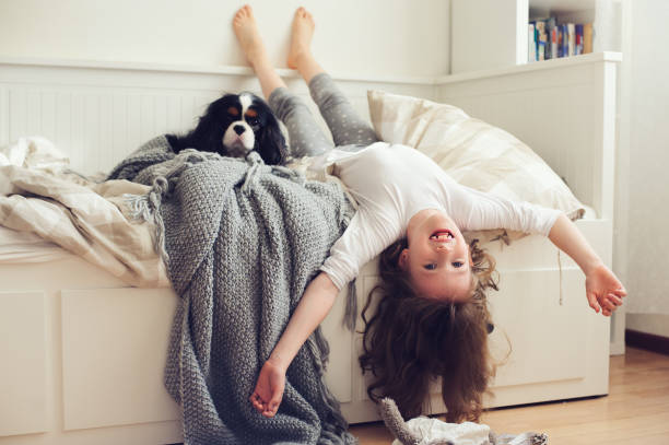 happy kid girl waking up in the morning in her bedroom with dog in bed stock photo