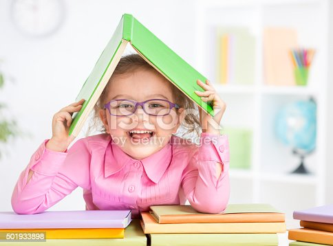 istock Happy kid in glasses under roof made from book 501933898