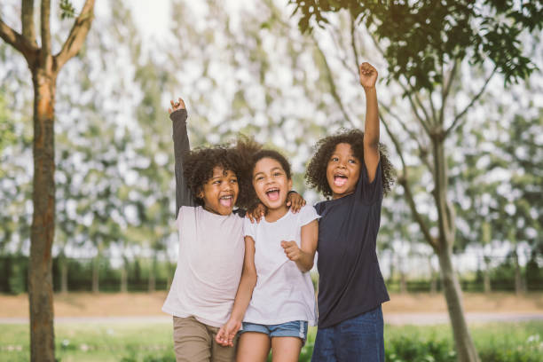happy kid joyful cheerful - african youth jumping for joy stock photos and pictures