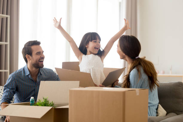 Happy kid jumping out of box laughing packing with parents Happy kid daughter jumping out of box excited about moving day or relocation, cheerful child girl playing unpacking in new home with mom and dad, smiling family laughing having fun packing together physical activity stock pictures, royalty-free photos & images