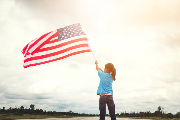 Happy kid little child standing with American flag USA celebrate 4th of July stock photo