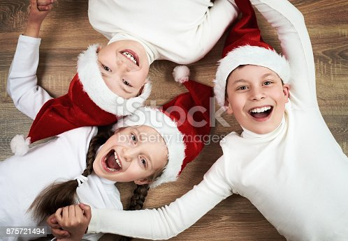 865399512istockphoto happy kid lying together on wooden background, dressed in christmas Santa hat and having fun, happy new year and winter holiday concept 875721494