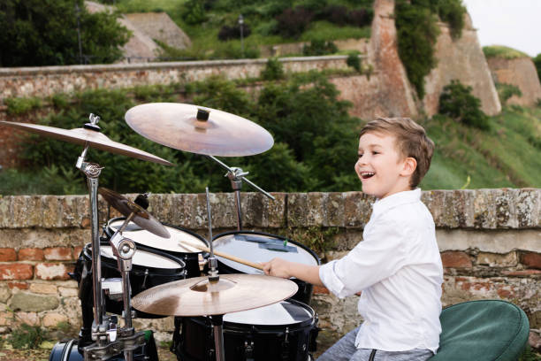 Happy kid playing drums outdoors.