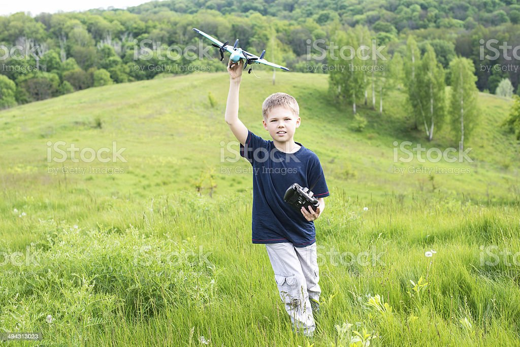 Happy kid playing with toy airplane against beautiful nature background. stock photo