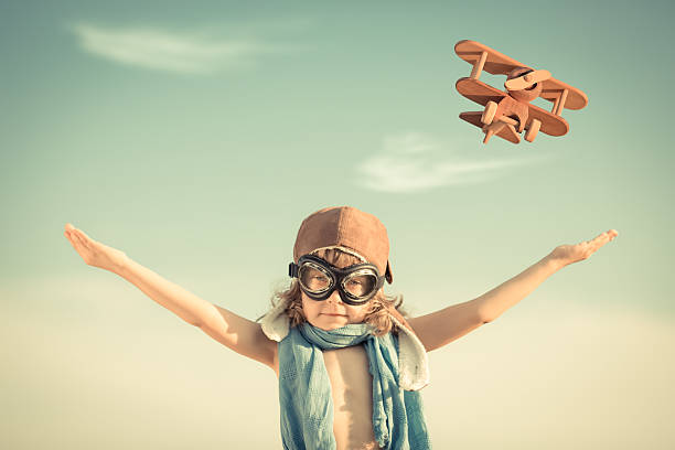 Happy kid playing with toy airplane stock photo