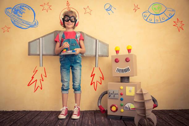 Criança feliz jogando com robô de brinquedo - foto de acervo