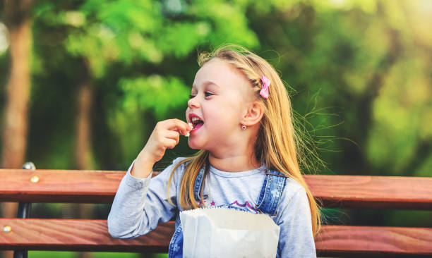 Happy kid sitting on the park bench and eating popcorn. Childhood, lifestyle concept stock photo