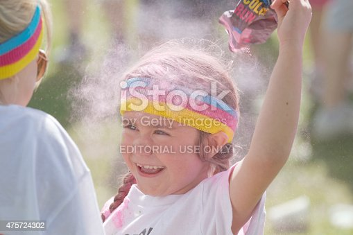 istock Happy kid squirting pink color powder over the head 475724302