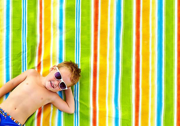 happy kid sunbathing on colorful blanket stock photo