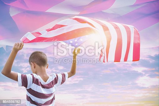 96695299 istock photo Happy kid with a hande held American flag in standing in the summer sunshine. USA celebrate 4th of July- Independence Day. 854559782