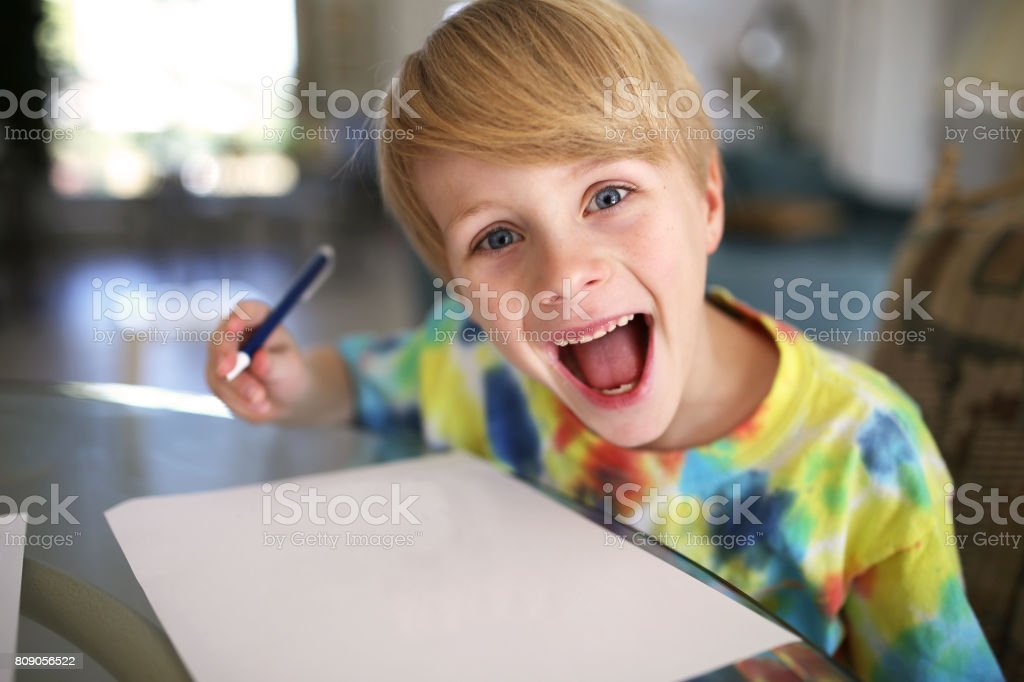 Happy Kid with Big Smile Drawing on White Paper with Pen stock photo