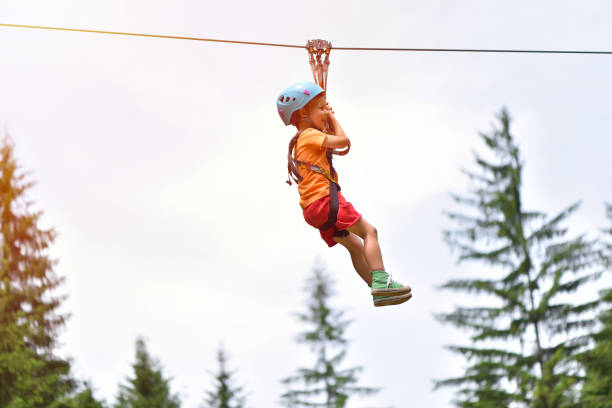 Happy kid with helmet and harness on zip line between trees Happy kid with helmet and harness on zip line between trees zip line stock pictures, royalty-free photos & images