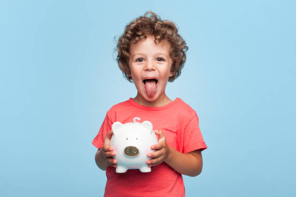 Happy kid with moneybox Charming boy holding piggybank and showing tongue at camera on blue background. protruding stock pictures, royalty-free photos & images