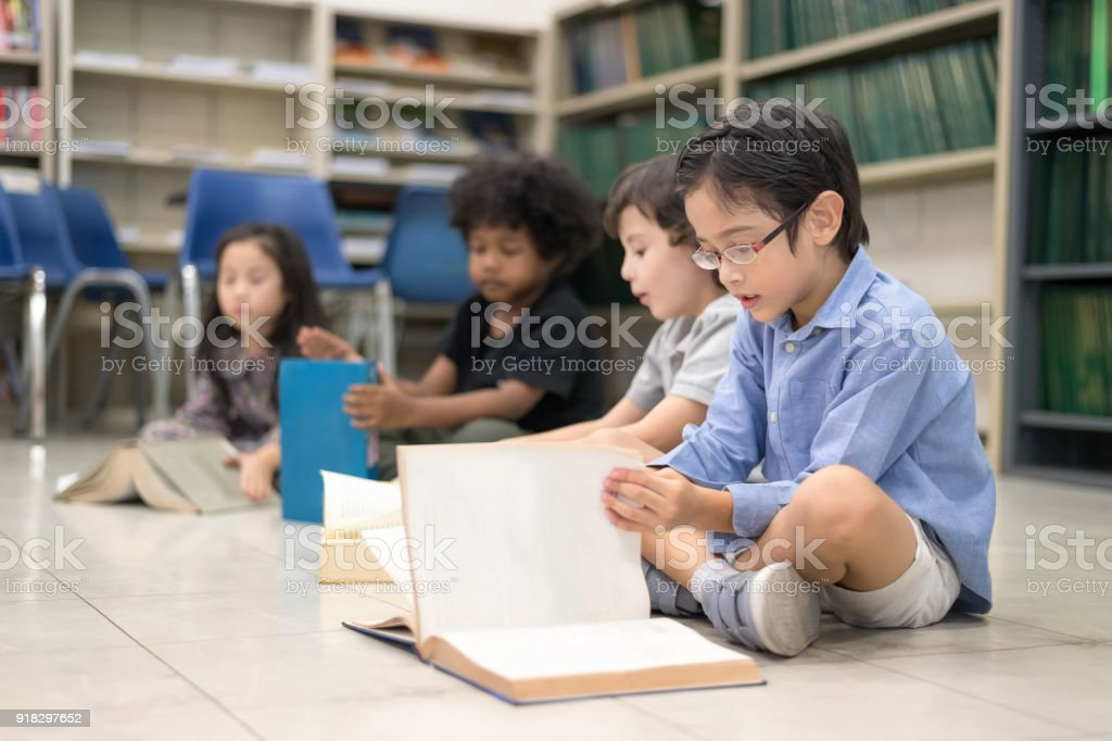 Happy kids and bored kids reading book on the floor, Education...