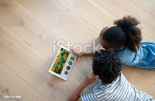 Happy kids at home watching videos on a tablet computer using headphones and smiling - lifestyle concepts. **IMAGE AND DESIGN ON SCREEN BELONGS TO US**