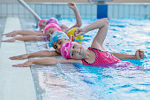 happy kids at the swimming pool. young and successful swimmers pose