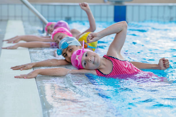 happy kids at the swimming pool. young and successful swimmers pose. - practising stock photos and pictures