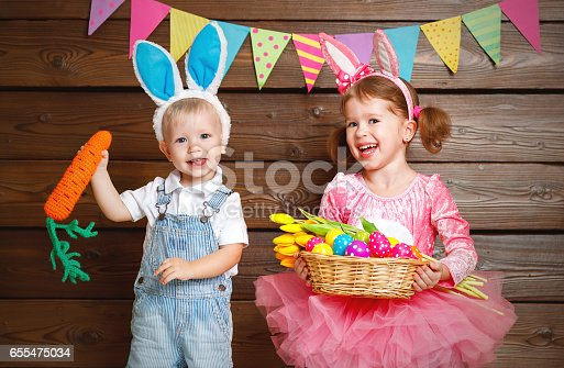 istock Happy kids boy and girl dressed as Easter bunnies with basket of eggs on  wooden 655475034