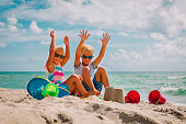 happy kids- boy and girl play with sand on beach vacation