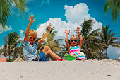 happy kids- boy and girl play with sand on tropical beach with palm trees