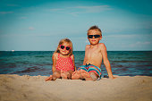 happy kids- boy and girl relax on beach vacation