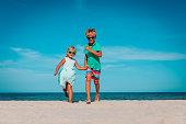 happy kids- boy and girl running at beach vacation