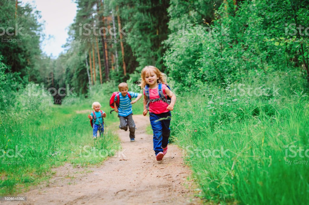 happy kids- boy and girls run to school stock photo