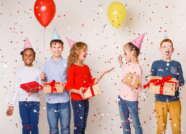 happy kids feiern geburtstagsparty über hintergrund - jugendliche geburtstag geschenke stock-fotos und bilder