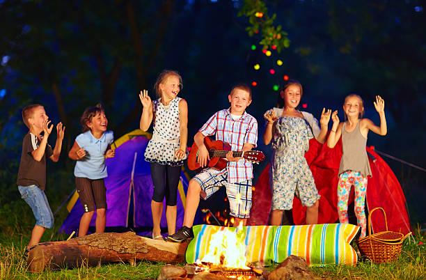 glückliche kinder tanzen rund um lagerfeuer - tanz camp stock-fotos und bilder