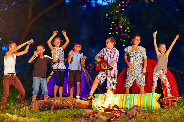 happy kids dancing around campfire stock photo