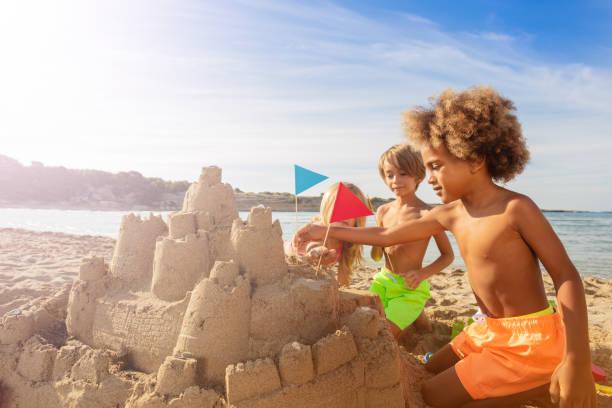 enfants heureux sandcastle tours avec des drapeaux de décoration - chateau de sable photos et images de collection