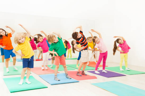Happy kids doing side bending exercises in gym stock photo