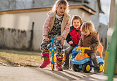 Small group of children enjoying a day outdoors on their vehicles.