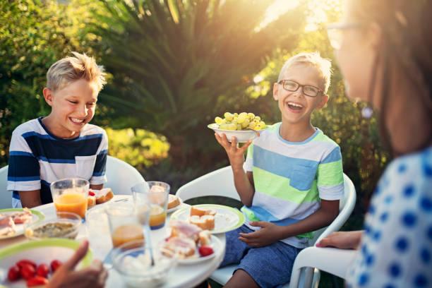 glückliche kinder frischverzehr frühstück im freien - mensch isst gras stock-fotos und bilder