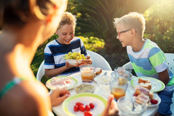 Happy kids eating fresh breakfast outdoors stock photo