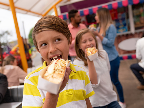 Portrait of happy kids eating junk food at an amusement park and smiling - lifestyle concepts