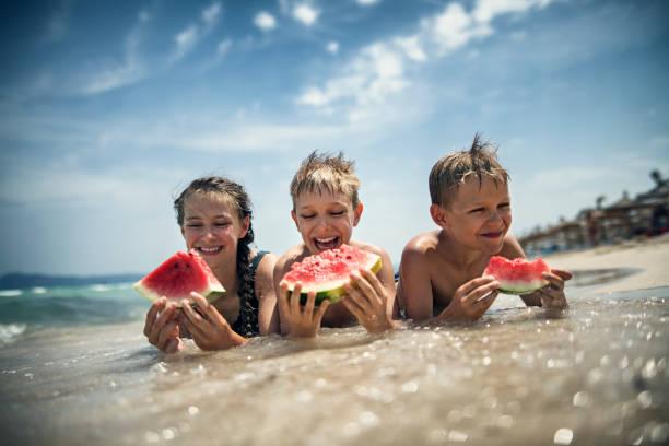 Glückliche Kinder essen Wassermelone am Strand – Foto