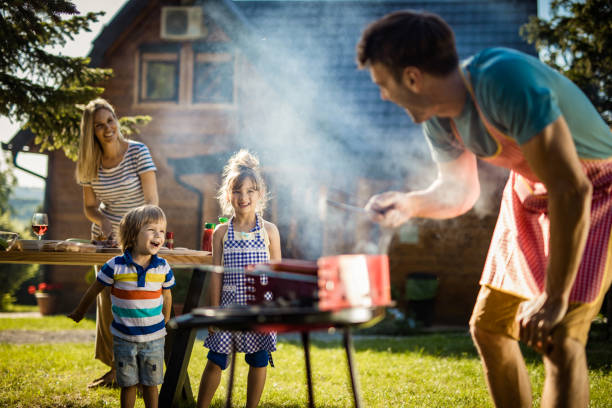 Happy kids enjoying in picnic day with their parents in the backyard. Happy little kids talking to their father while he is preparing barbecue. Focus is on kids. family bbq stock pictures, royalty-free photos & images