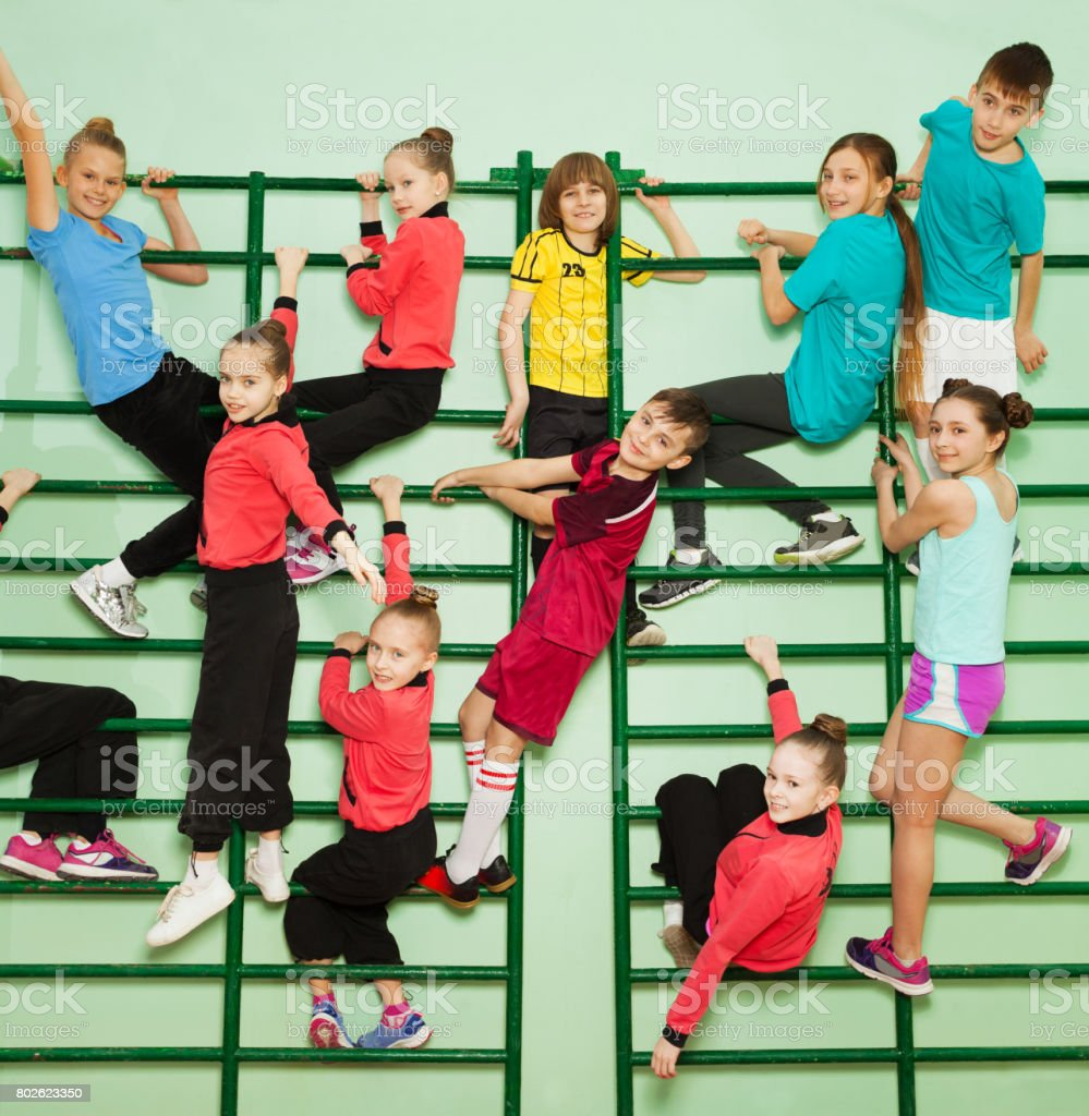Happy kids exercising on wall-mounted gym ladder stock photo